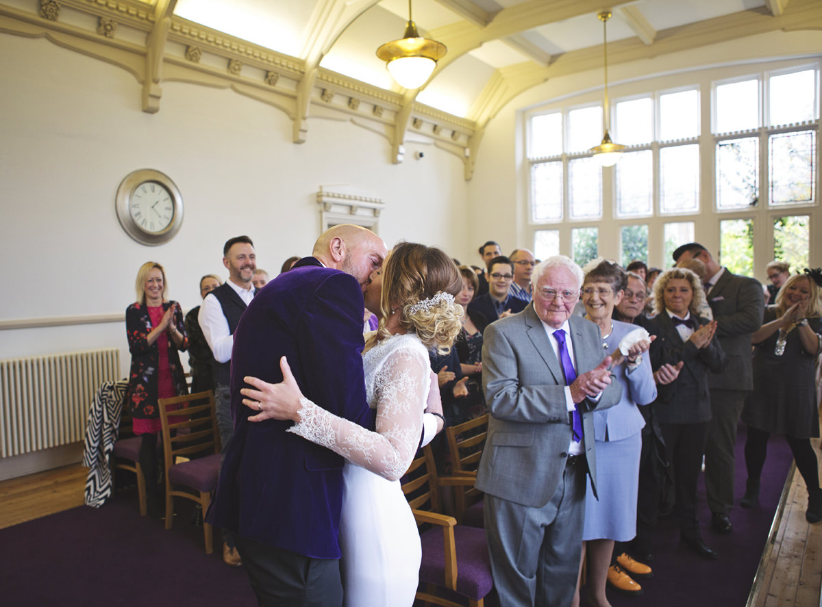 Newlyweds kiss as their guests applaud at a wedding ceremony