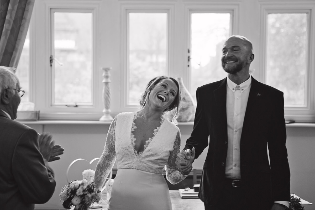 A bride and groom laugh as they face their guests at the end of their wedding ceremony