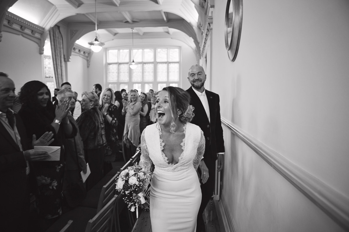A bride laughs as she exits the registry office with her husband while their guests applaud