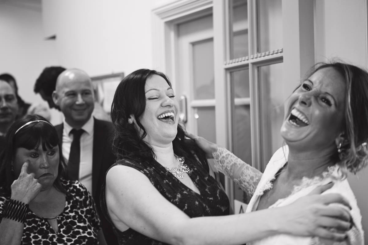 A bride bursts out laughing with a friend during the lineup at her wedding