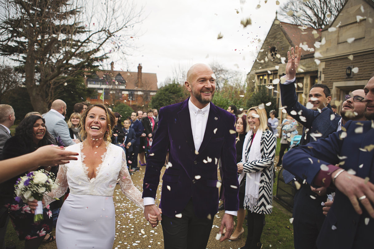 Newlyweds laugh as they have confetti thrown over them by their wedding guests
