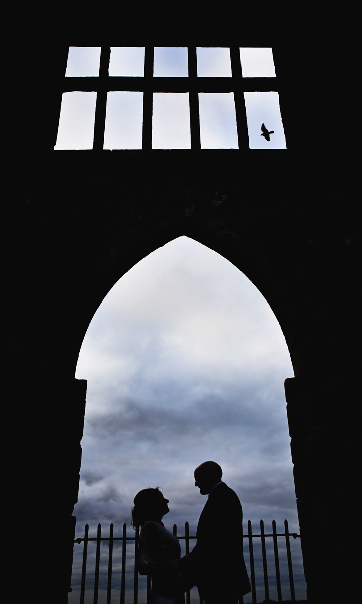 A silhouette of a wedding couple standing in front of a castle battlement with a bird flying past a window