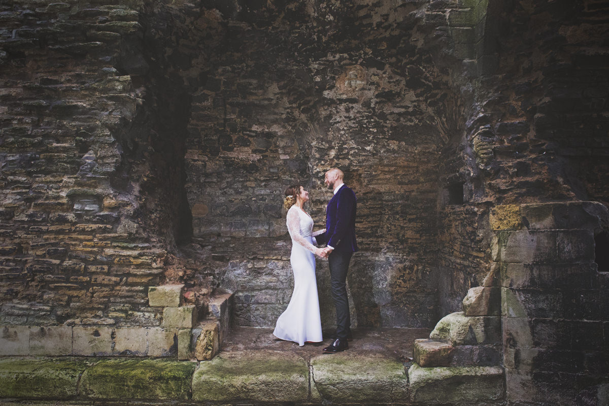 A bride & groom face each other and smile while stood amongst the ruins of Newark Castle