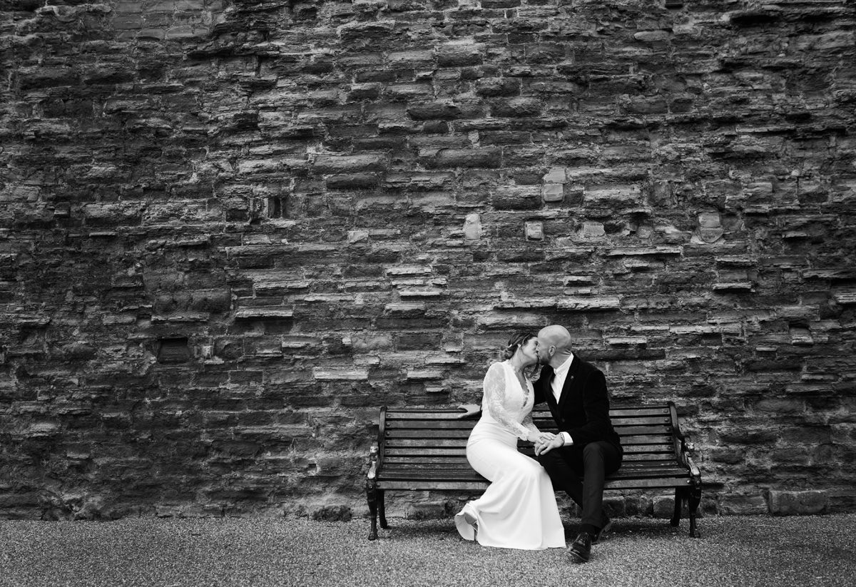 Newlyweds kiss while sat on a bench in front of an old castle wall