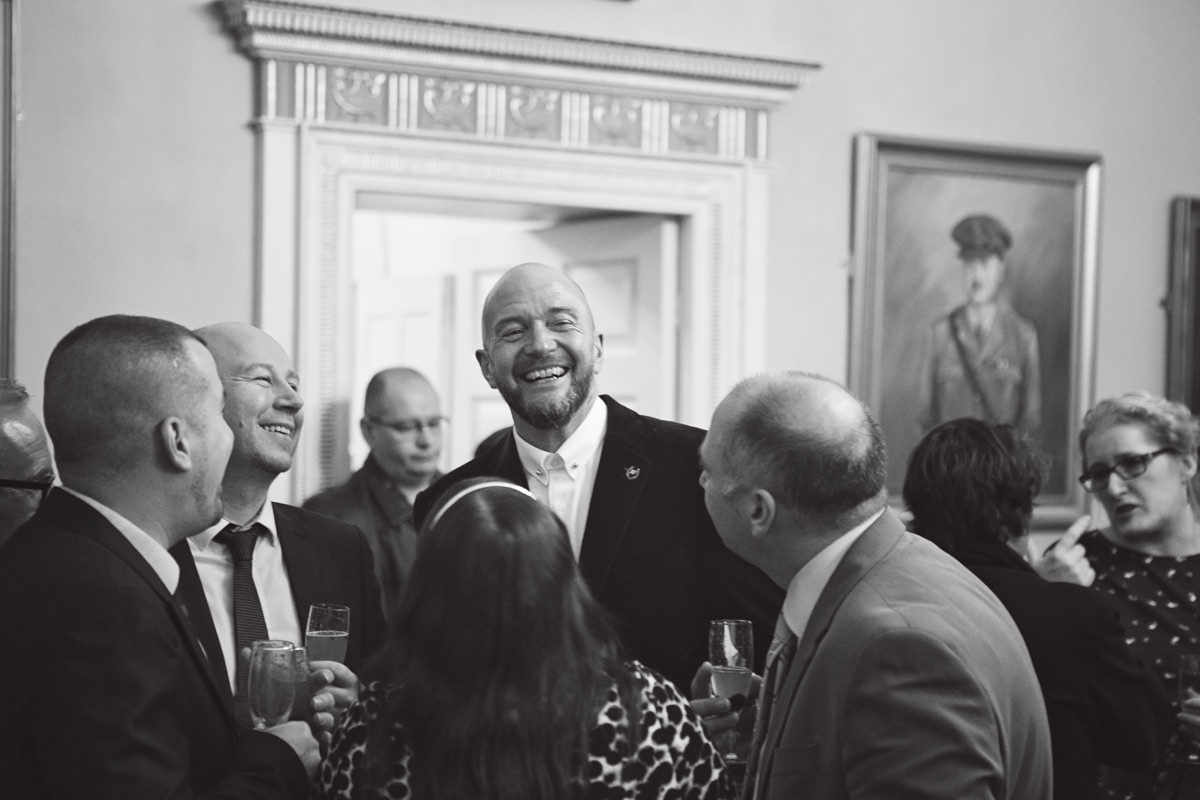 The groom shares a joke over drinks with his friends at his wedding reception