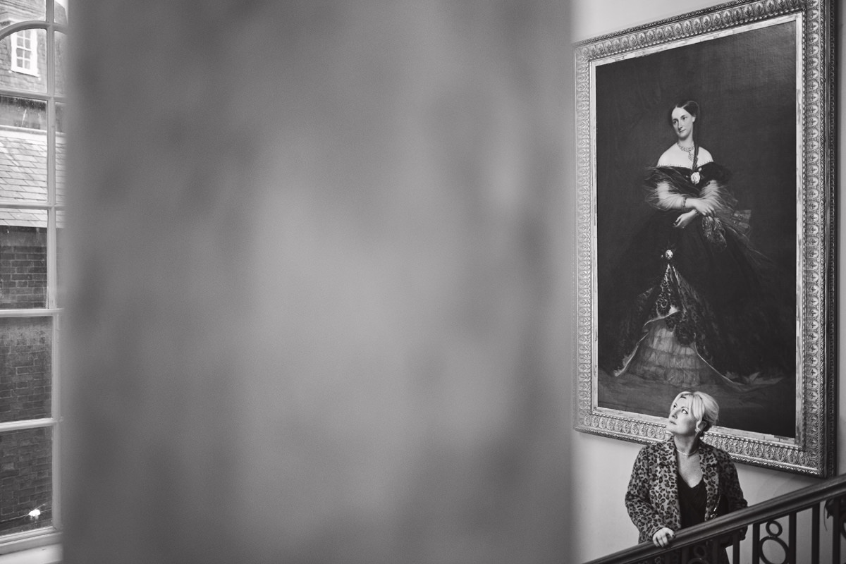 A black & white image of a women standing at the top of a large staircase admiring the old paintings in a grand hall