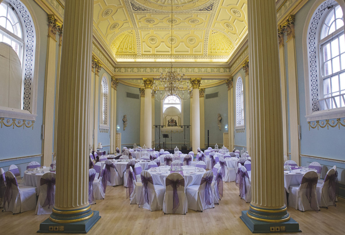 A wide shot of a grand hall with four pillars and tables set for a wedding reception