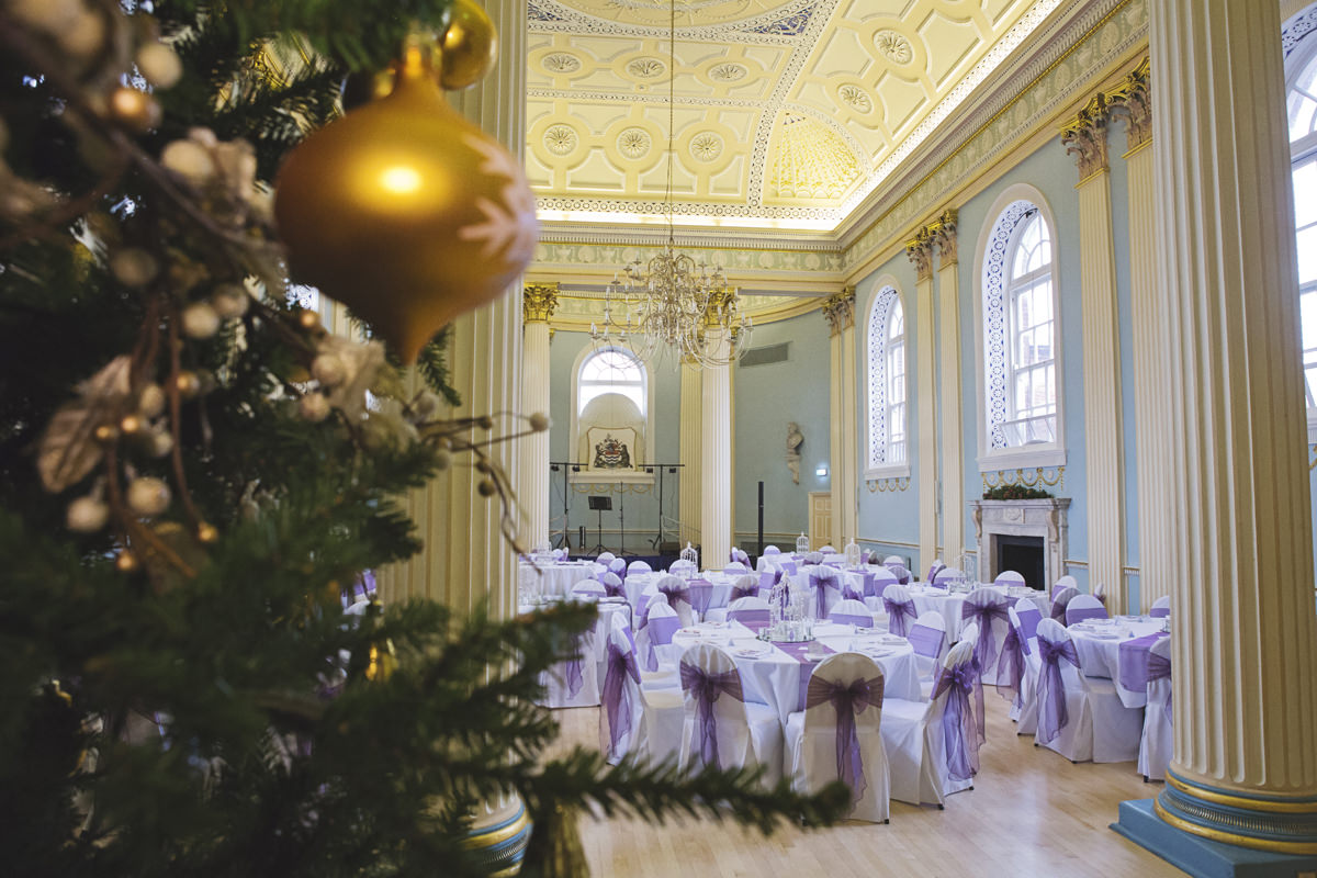 A wide shot of a grand hall with pillars and ornate ceiling set for a wedding reception with a christmas tree in the foreground
