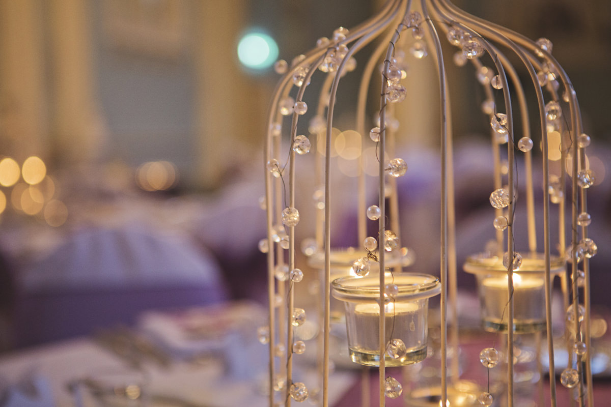 A close up shot of a candle table decoration with pearl fairy lights