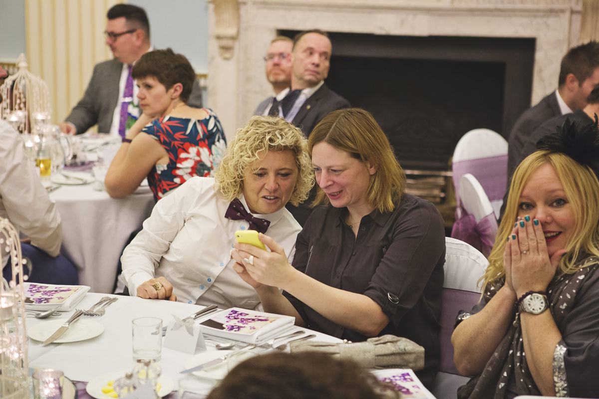 Two women looking at pictures on a phone while sat at a table during a wedding breakfast