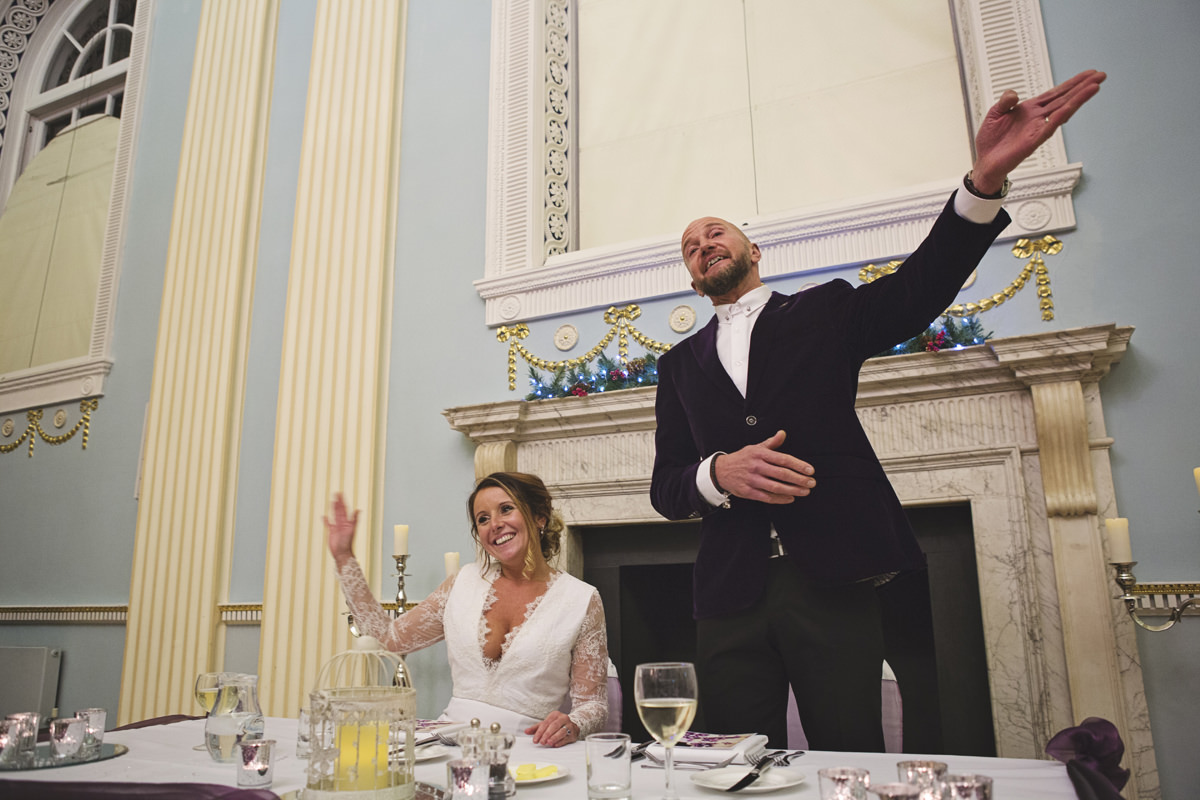 A bride waves while the groom points during his wedding speech