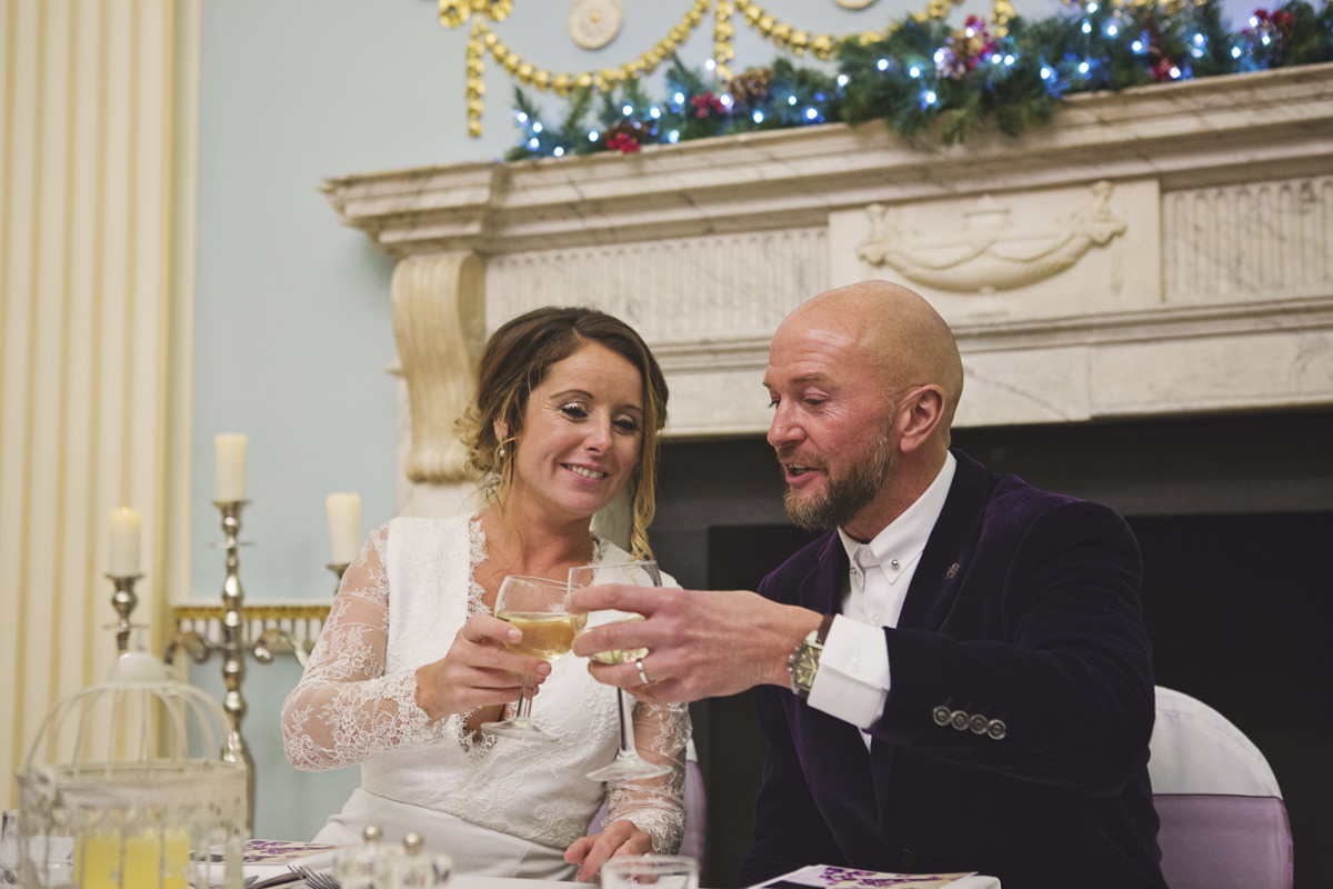 Newlyweds share a toast with each other at their table during their wedding breakfast