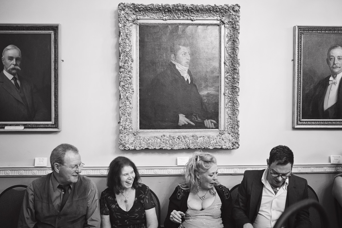 A wide shot of four wedding guests sat underneath three old portrait paintings at a wedding