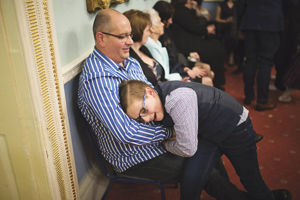 A young lad head barges his father in play at a wedding reception
