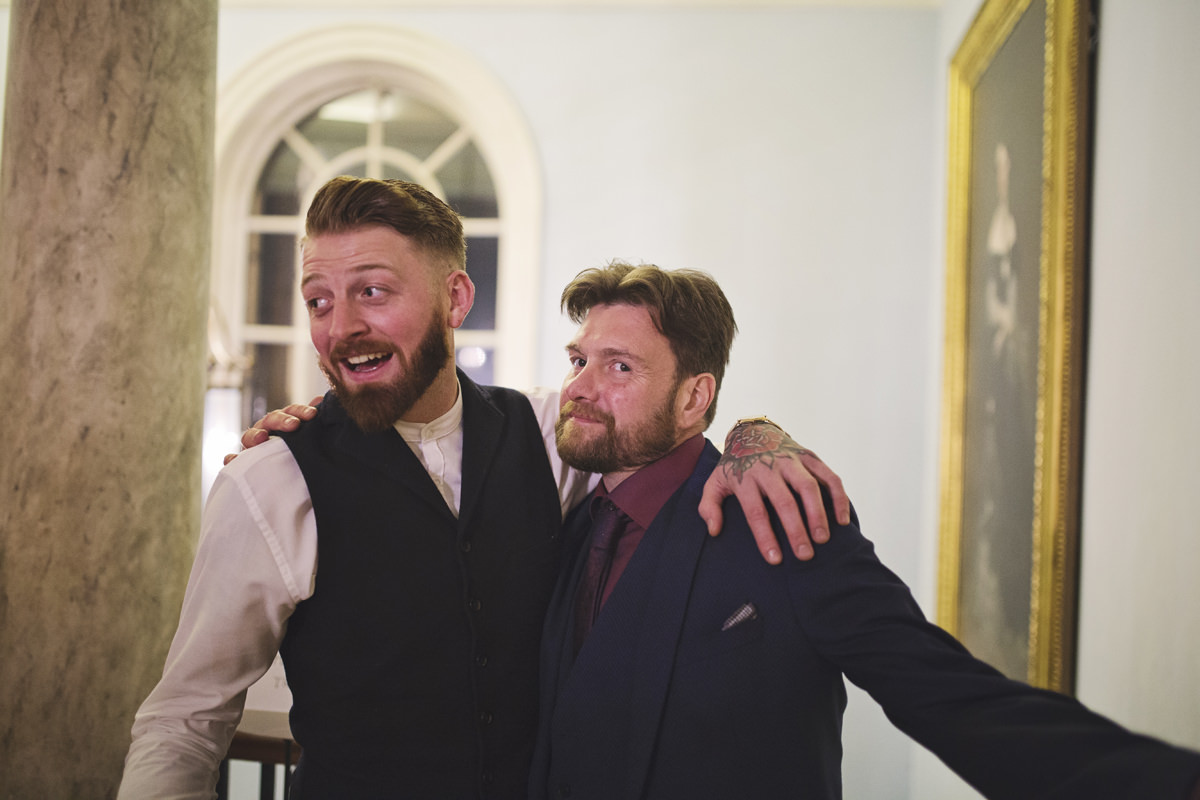 Two men embrace each other while smiling at a wedding reception