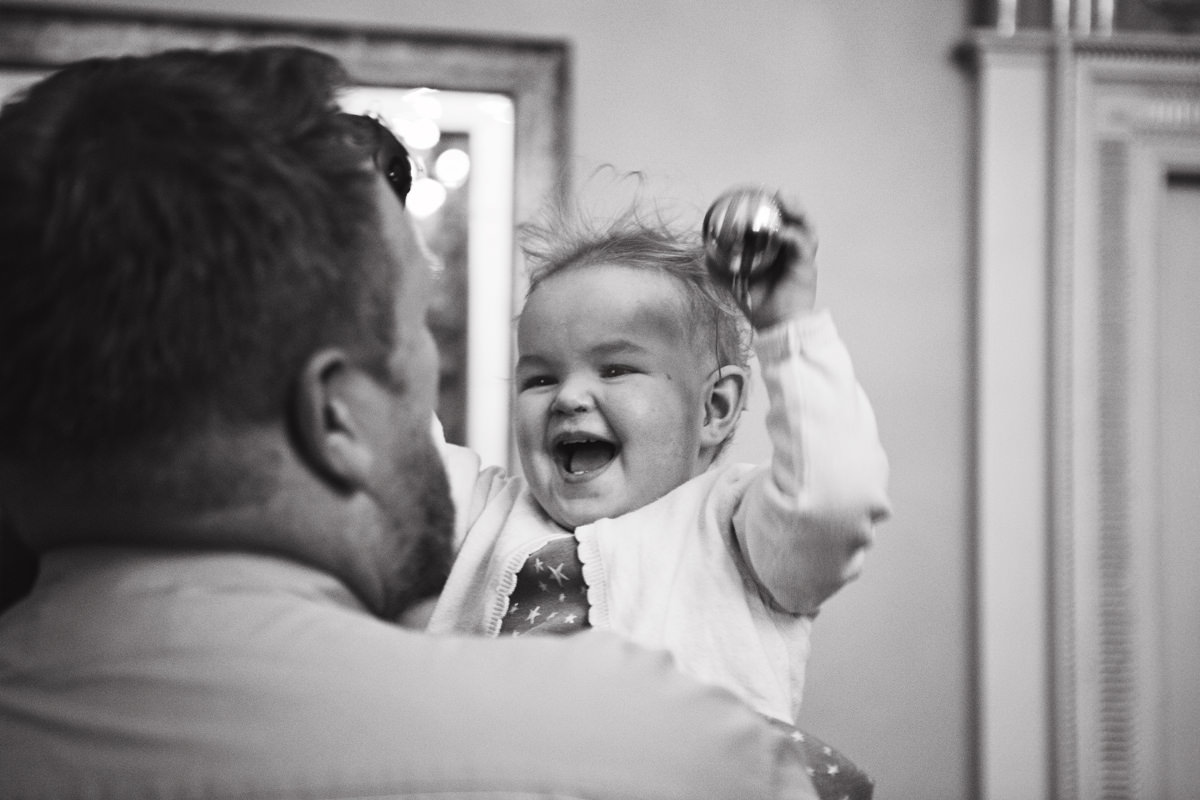 A baby girl laughs while being held by her dad as she plays with a christmas bauble