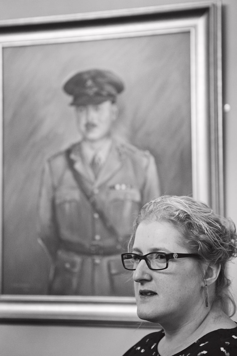 A lady wedding guest looks off camera with a portrait of a WW2 soldier in the background