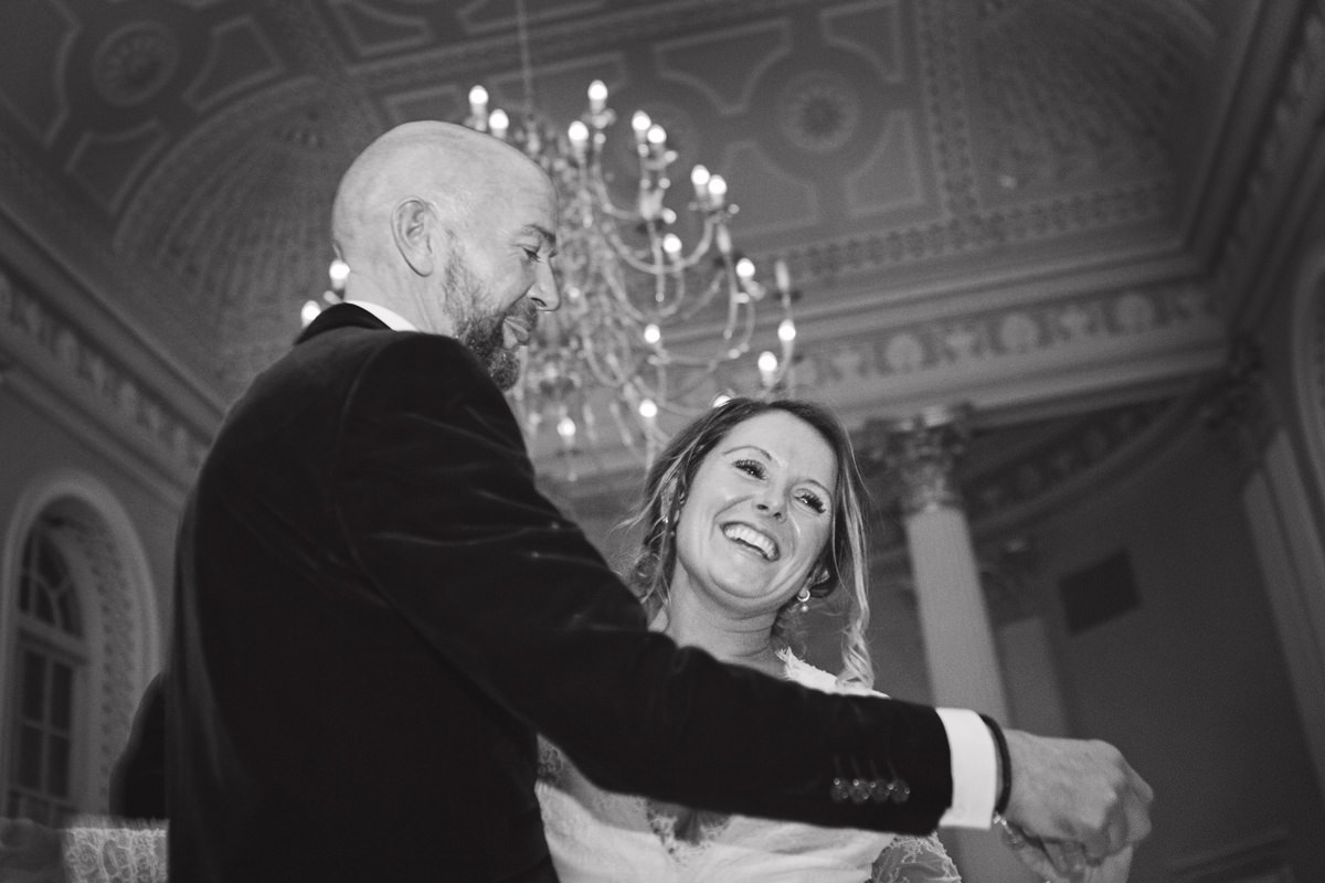 A bride facing the camera smiles as her groom dances with her