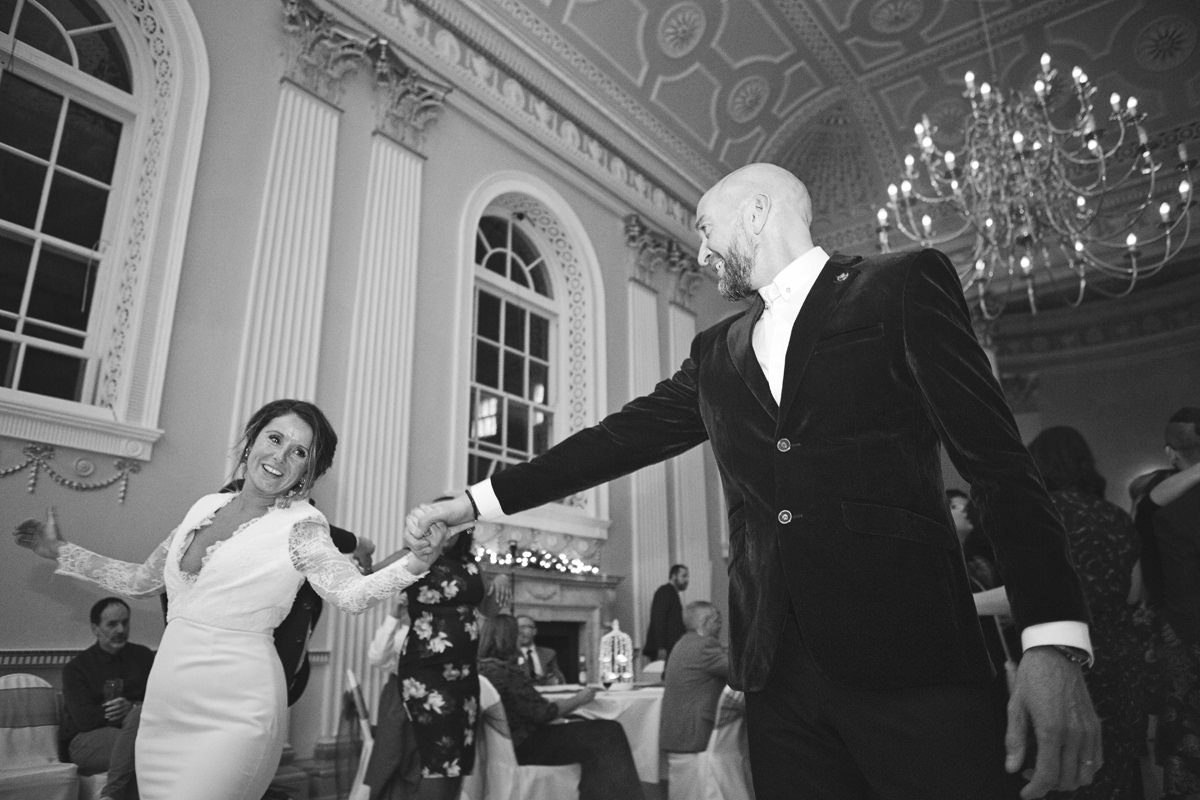 A bride and groom smile at each other during their first dance
