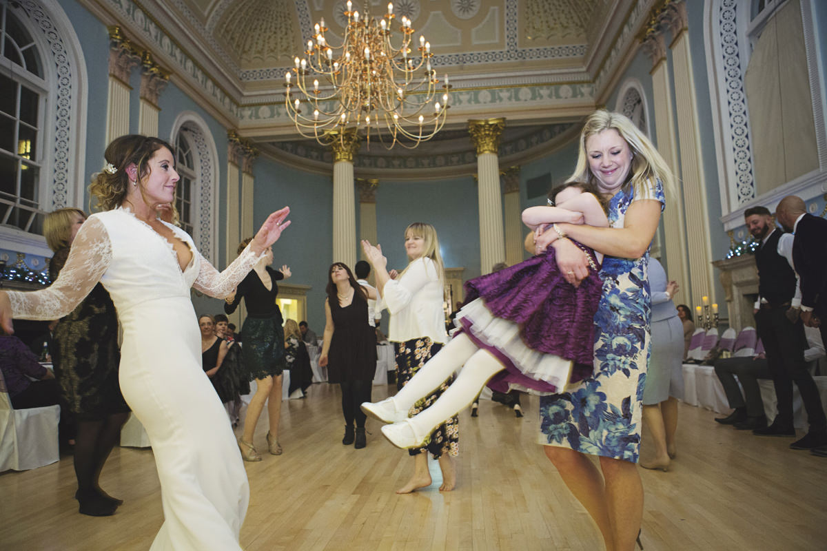 A woman holding a little girl spins her around as a bride dances at a wedding reception