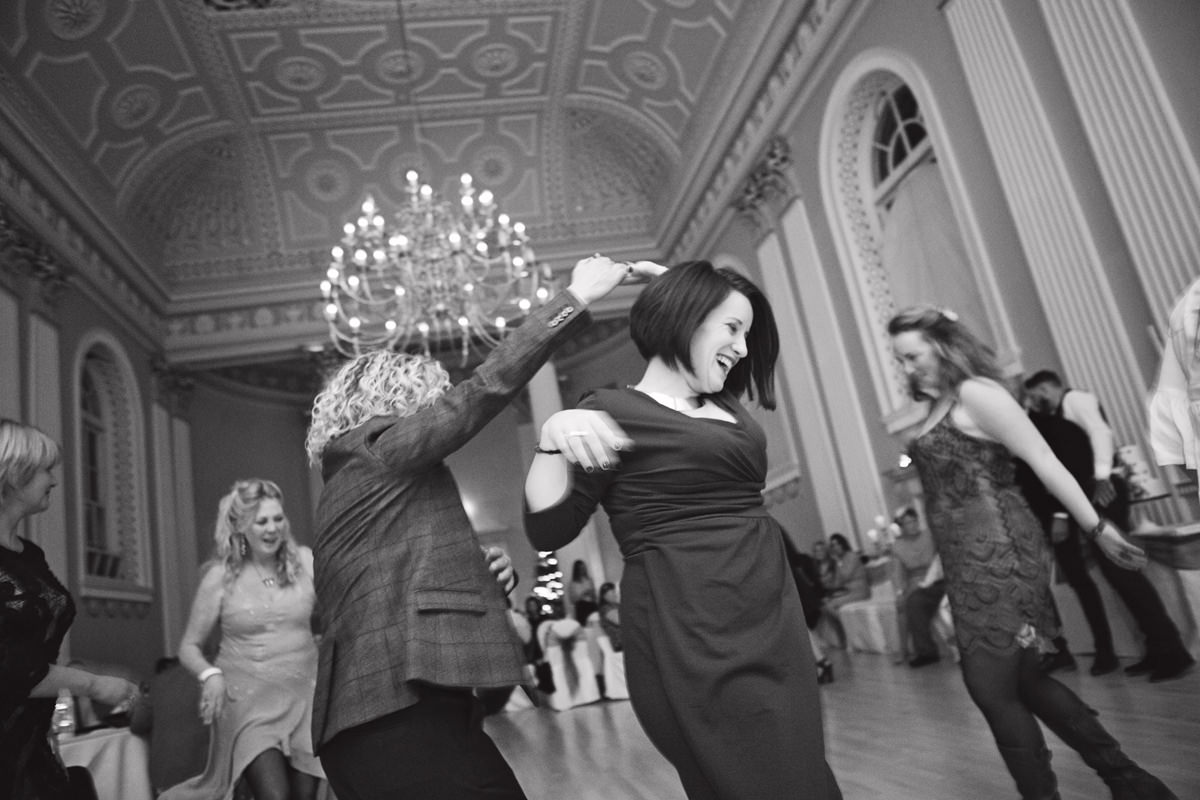 A shot of women twirling on the dance floor at a wedding