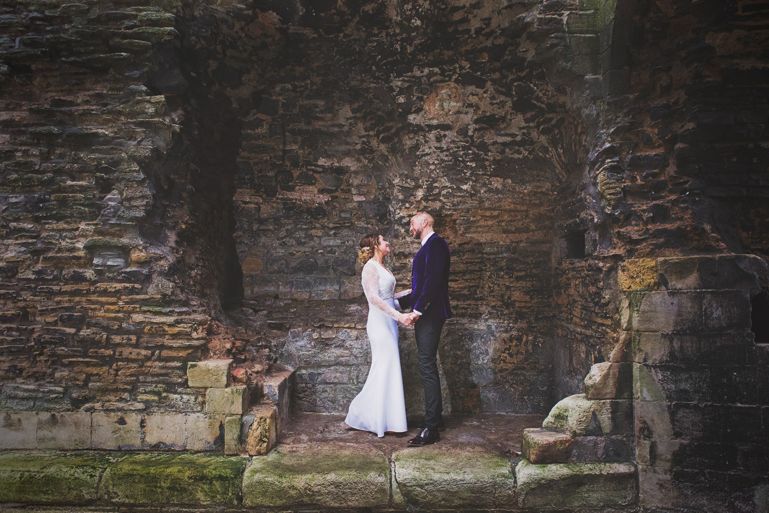 A newlywed bride and groom stood in a heart shaped alcove among the ruins of Newark Castle