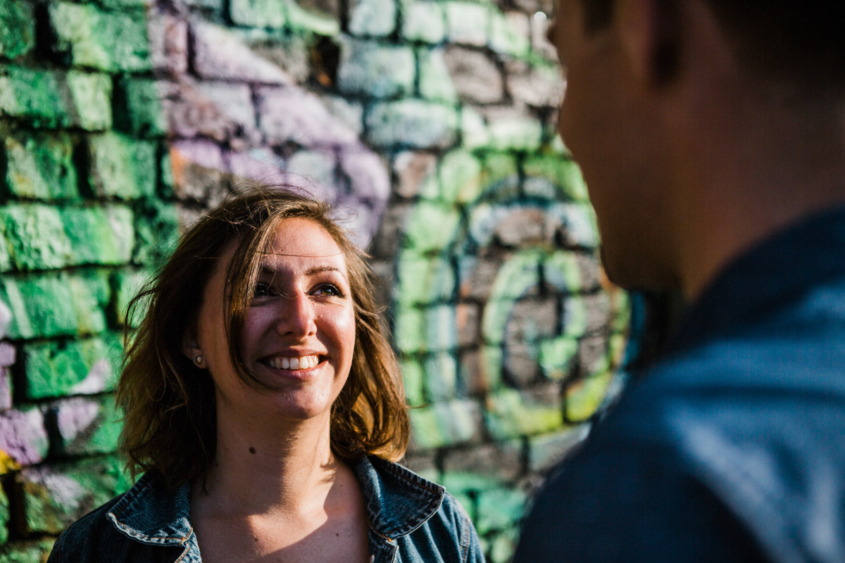 A young woman looks up at her fiancé while standing in front of a graffiti wall in Liverpool
