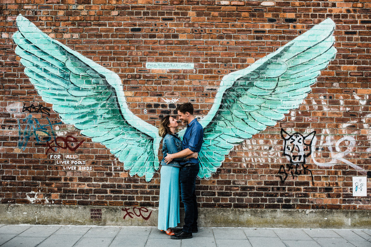 A young couple embrace in front of graffiti depicting a pair of wings in Liverpool