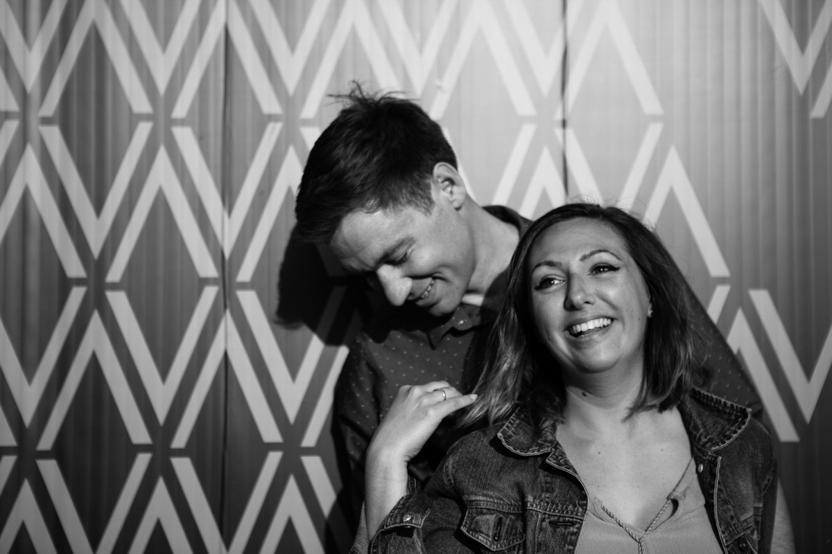 A black & white image of an engagement couple laughing while stood in front of a patterned wall