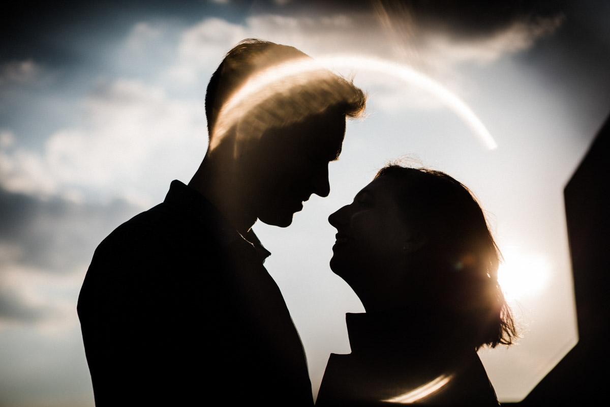 A silhouette of a woman and man facing each other with a ring of sun flare circling them