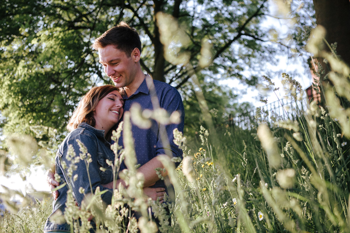 A newly engaged couple embrace surrounded by grass and trees in Liverpool