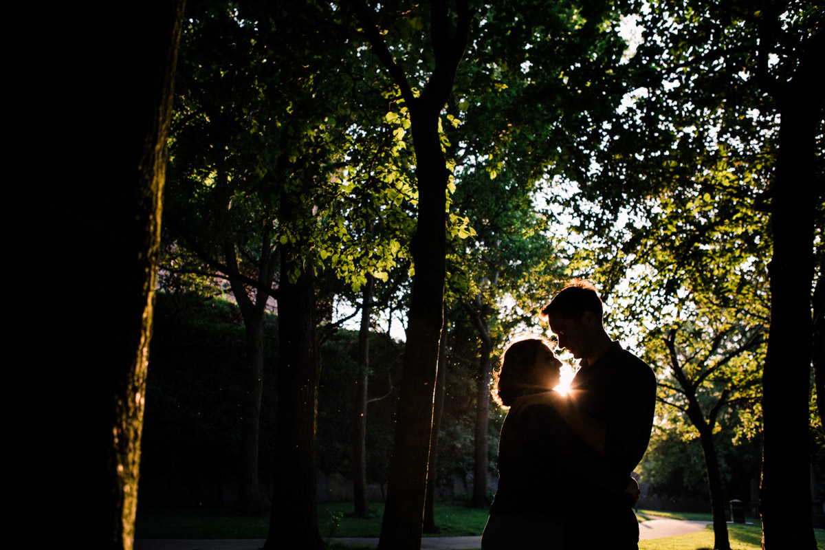A silhouette of a newly engaged couple standing in a park