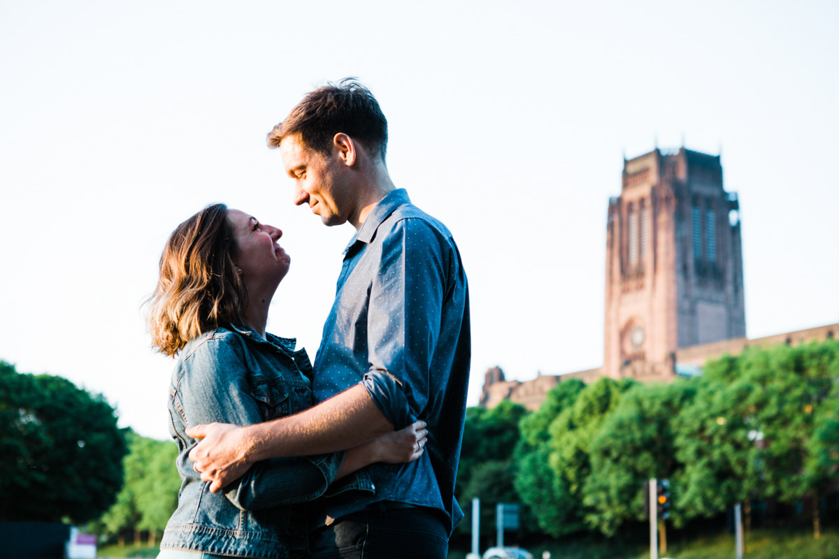 Newly engaged couple embrace with Liverpool Cathedral in the background