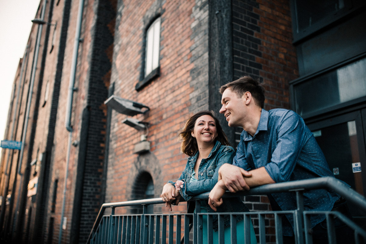 A young couple laugh as they lean on railings in Liverpool