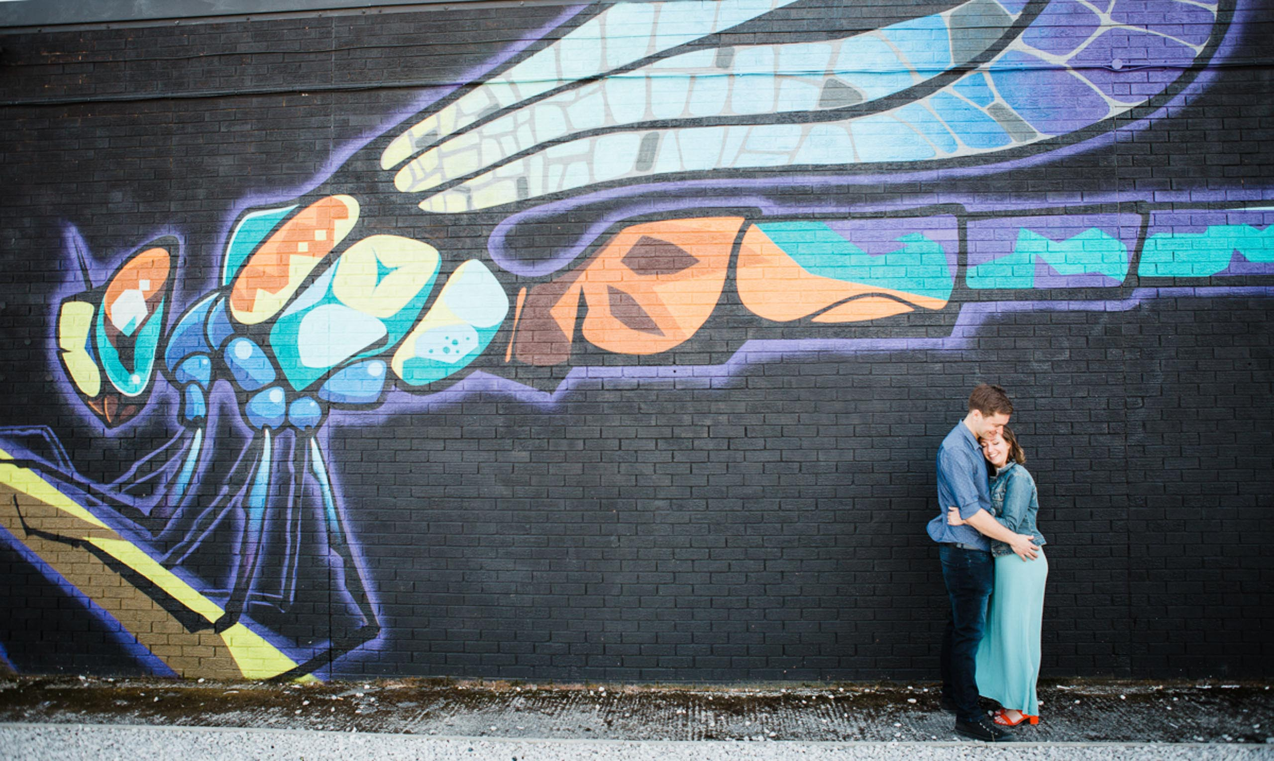 A young couple embrace white stood in front of a graffiti wall depicting a dragonfly