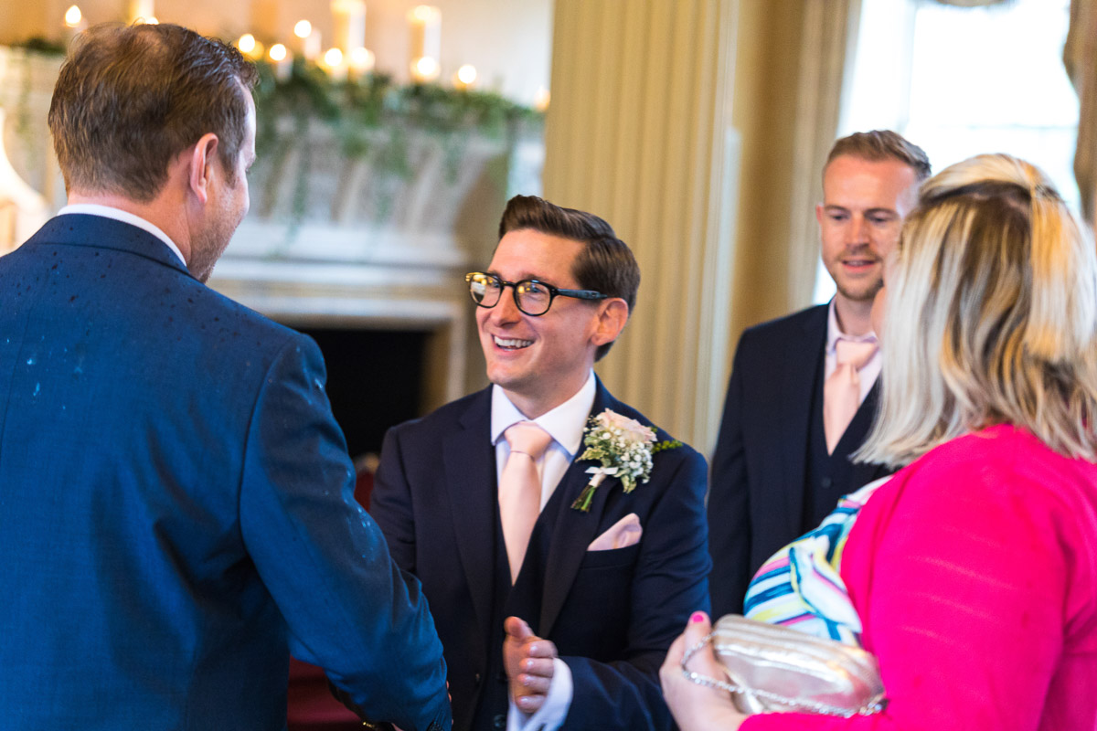 A groom welcomes guests before his wedding