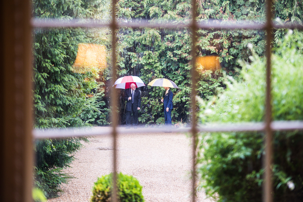 A shot looking through the window of two male wedding guests in a garden