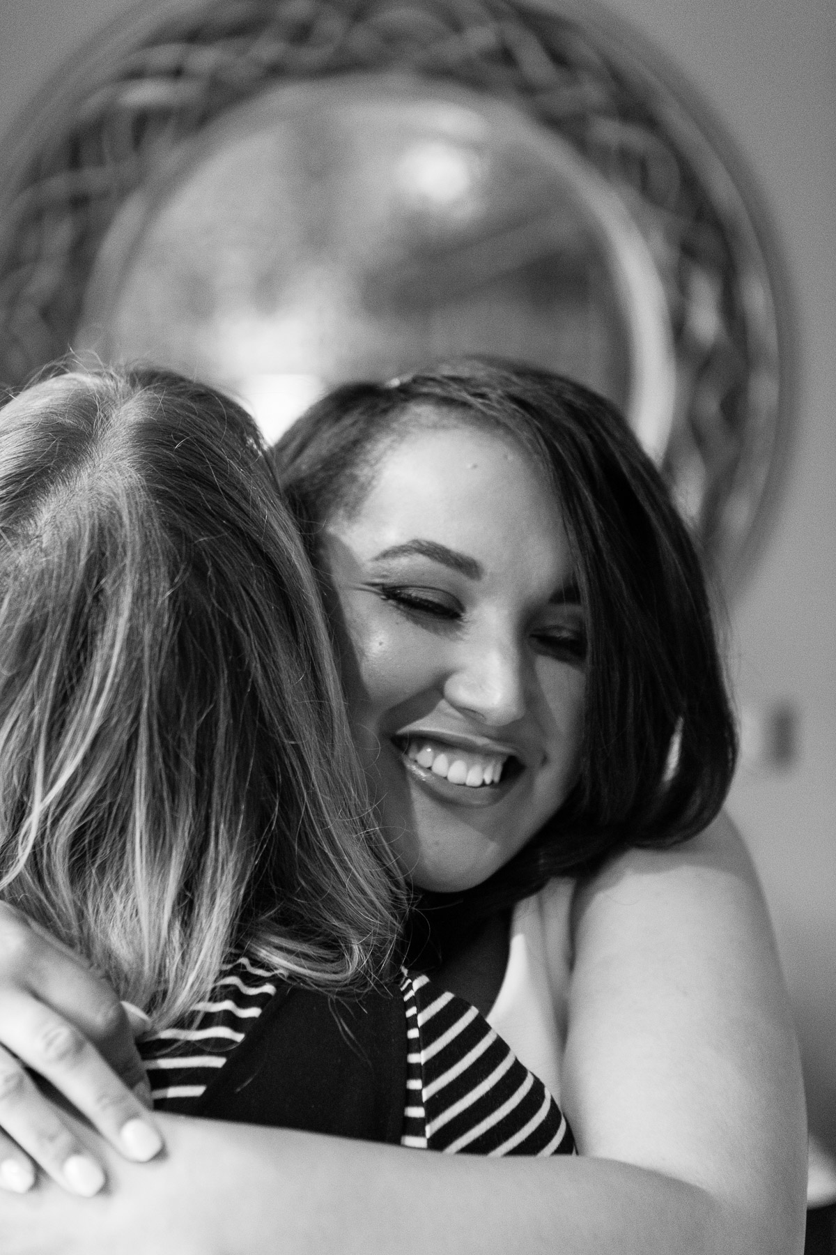 A black & white image of a bride hugging a friend