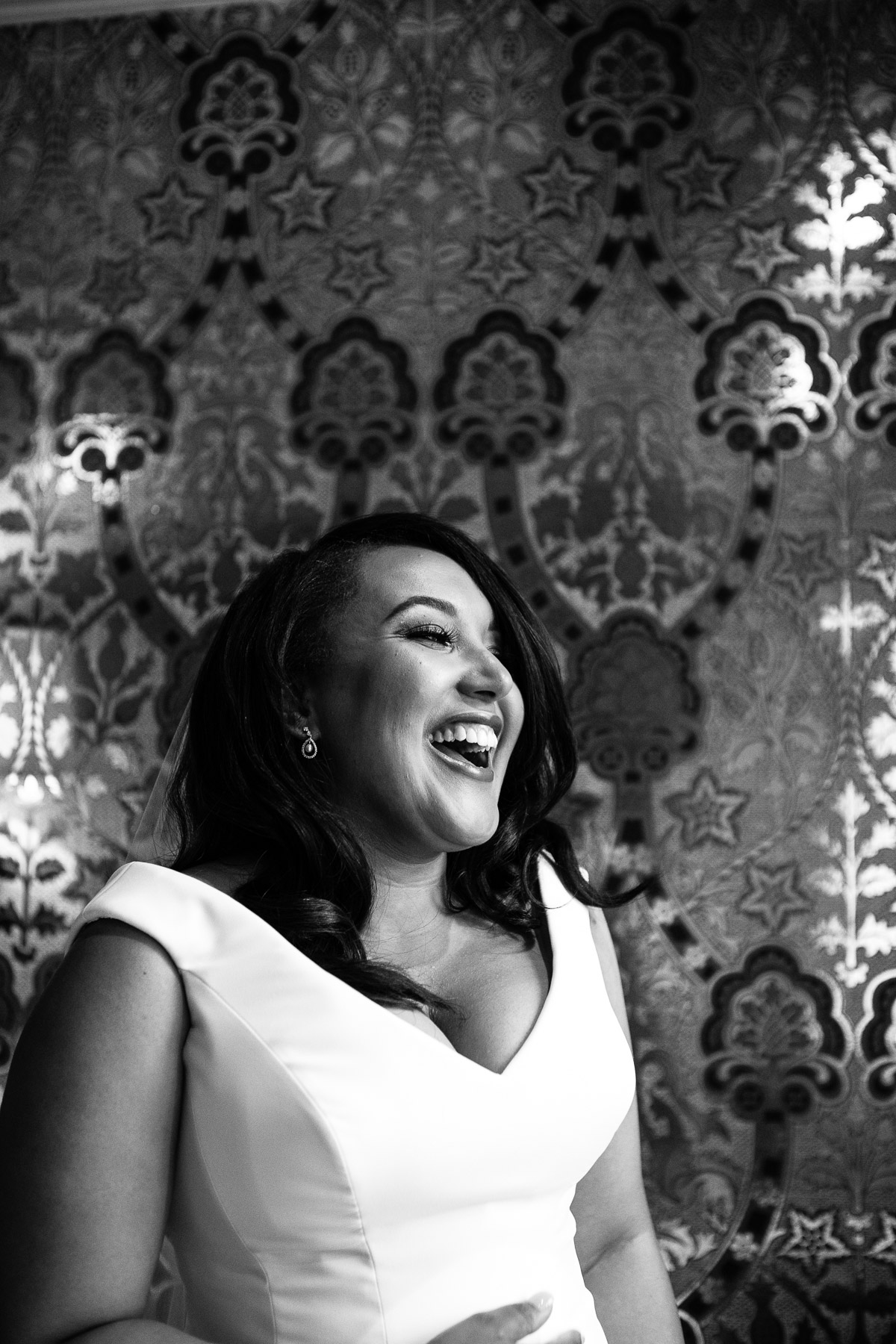 A black and white shot of a laughing bride stood in front of patterned wallpaper