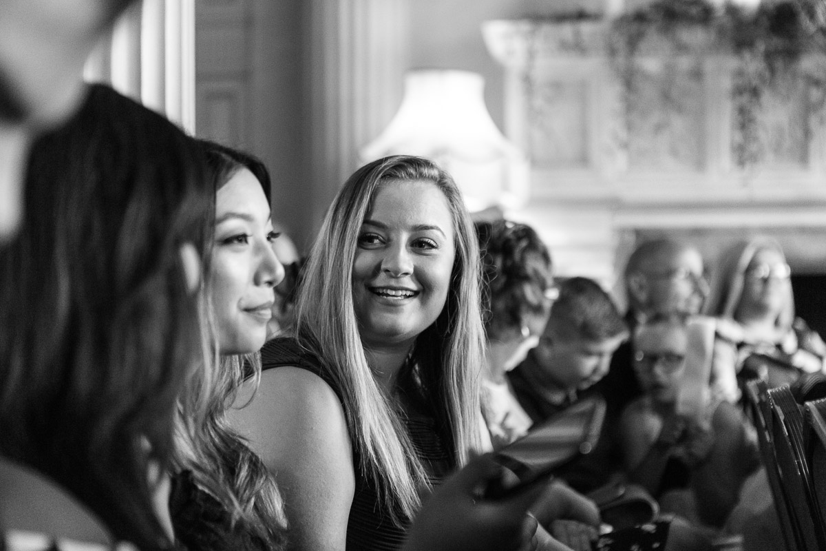A black and white shot of wedding guests chatting as they wait for the bride at the ceremony