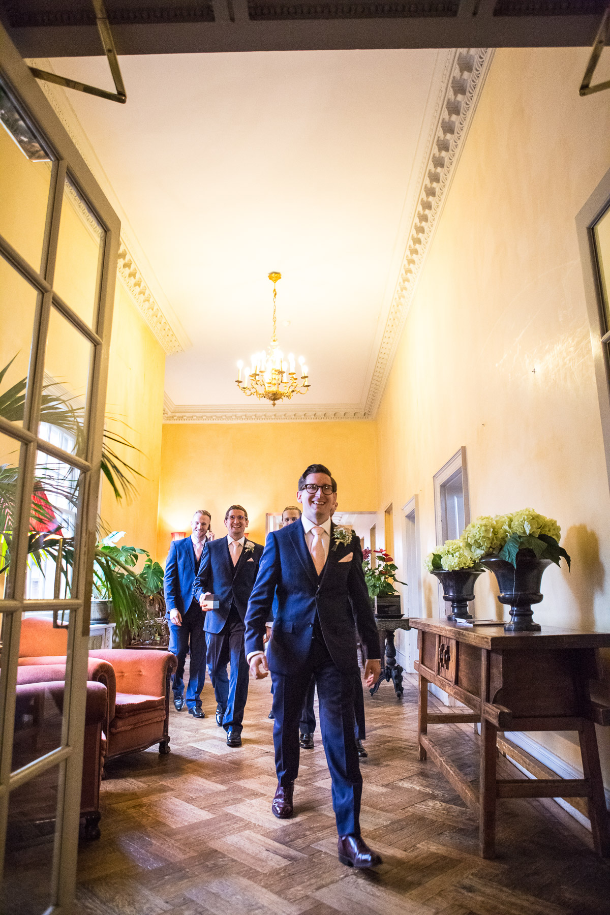 A Groom and his groomsmen walk along a corridor on the way to his wedding ceremony