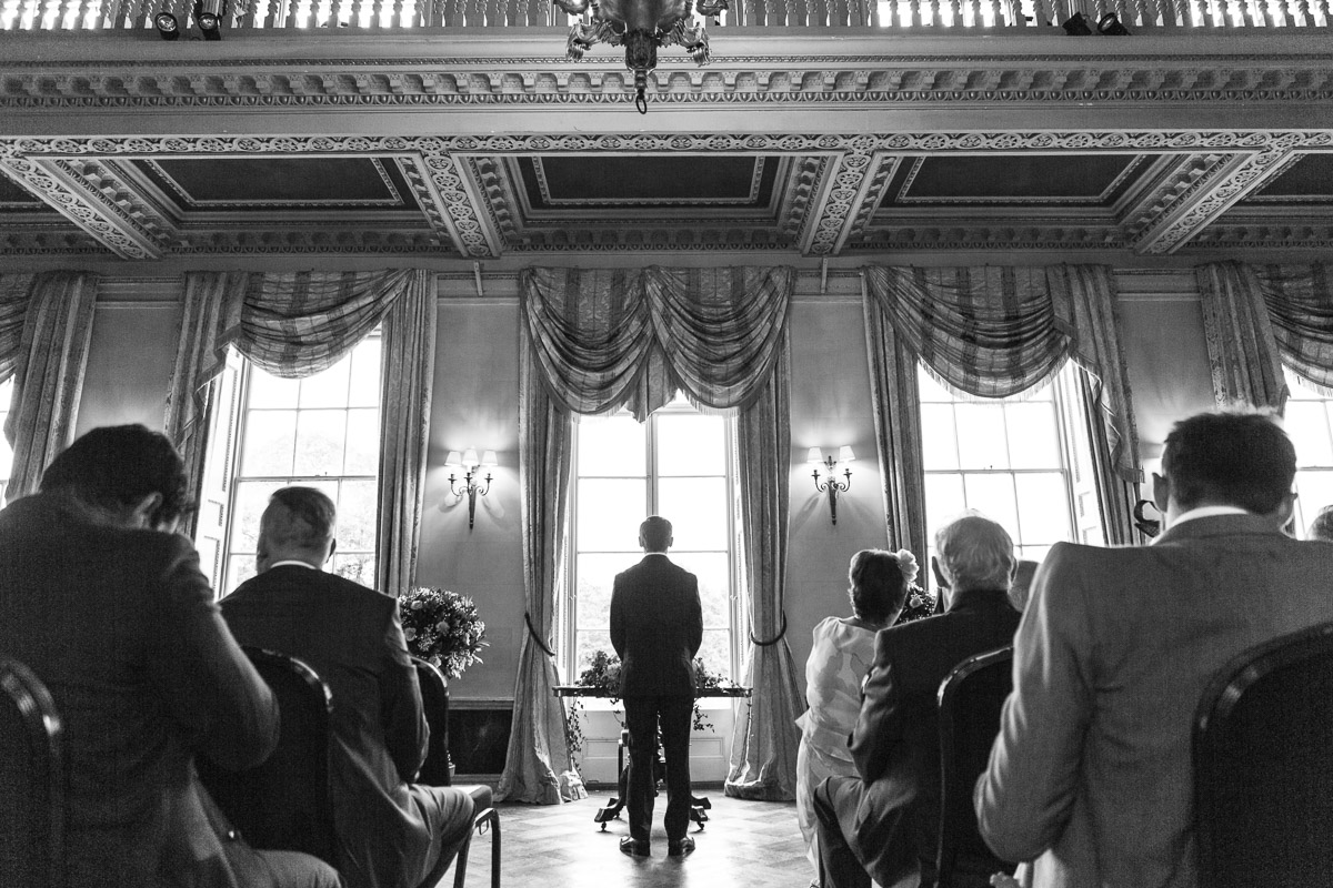 A black and white image from behind the groom as he stands alone at the alter surrounded by seated guests awaiting his bride.
