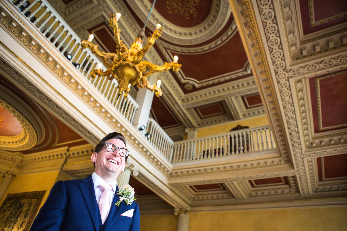 A low angle shot of the groom waiting to be married showing the ornate ceiling and chandelier in the hall