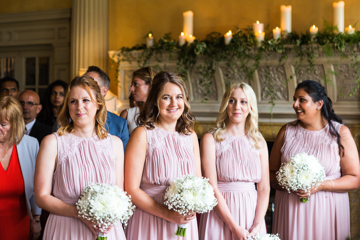 smiling bridesmaids in pink dresses await the bride at the alter