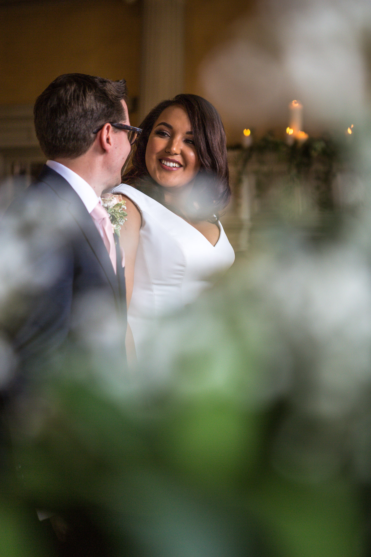 A bride & groom smile at the alter surrounded by blurred flowers