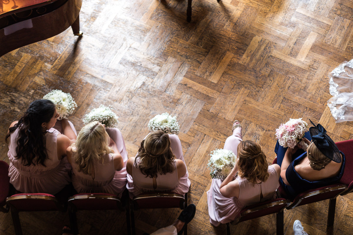 An overhead shot of bridesmaids sat during a wedding ceremony at Hampton Court House