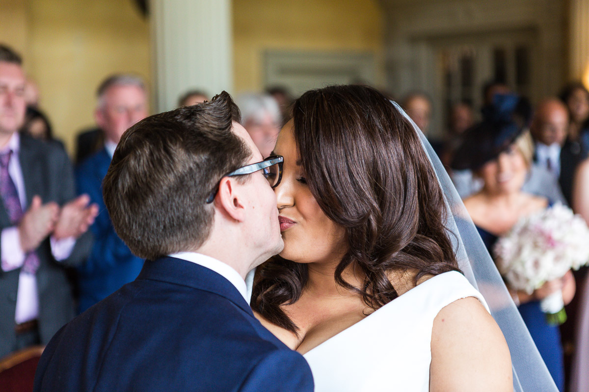 Newlyweds share a first kiss at their ceremony in Hampton Court House