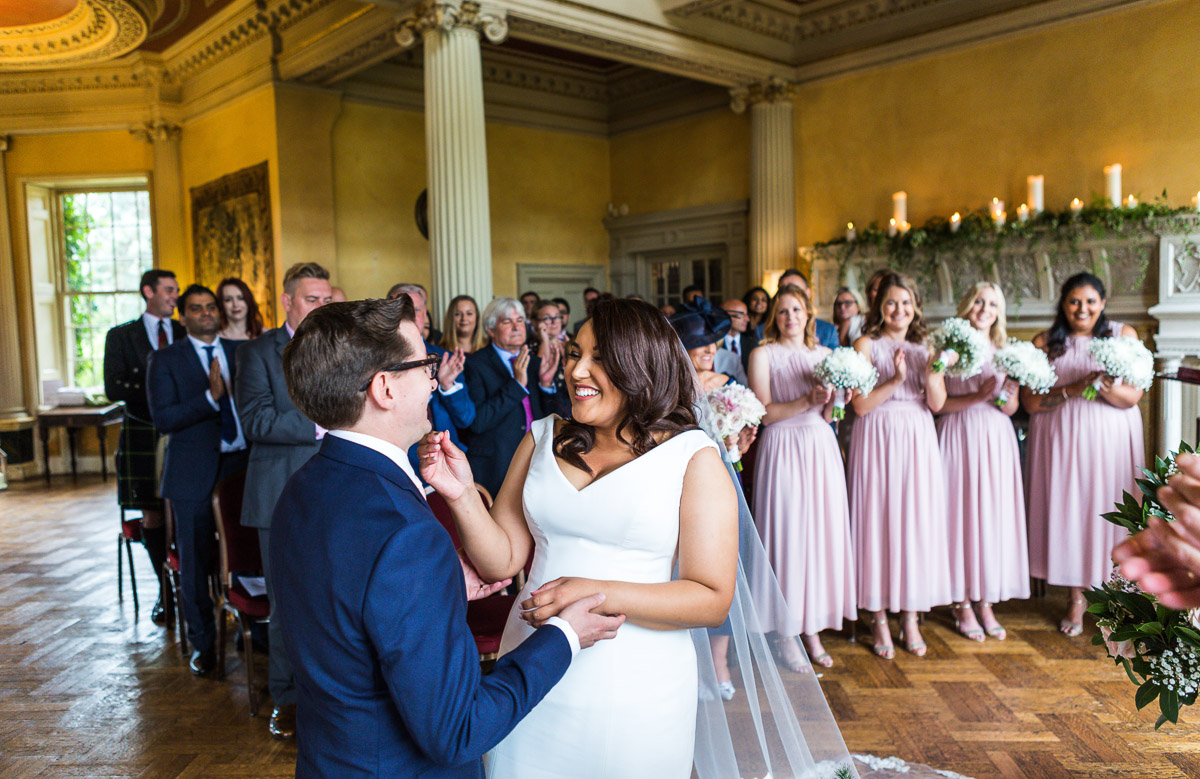 A newlywed couple laugh as their guests clap at their wedding ceremony in Hampton Court House