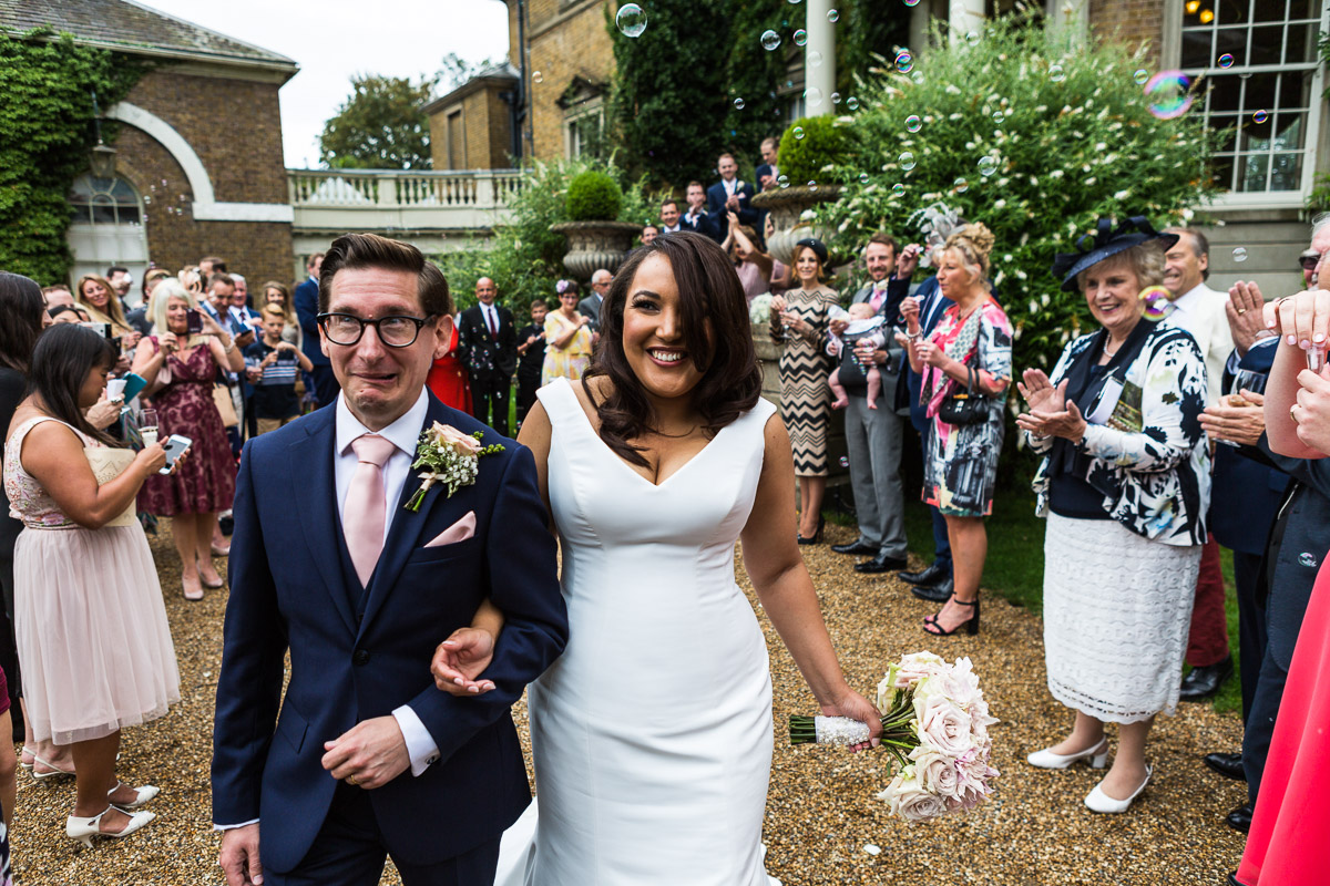 A groom pulls a funny face as newlyweds smile surrounded by their guests at Hampton Court House