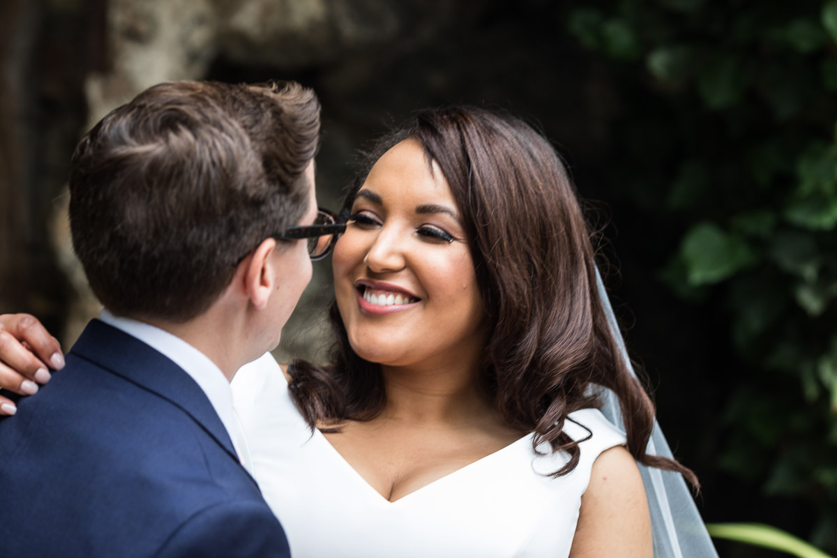 A close up of a bride smiling at her new husband on their wedding day